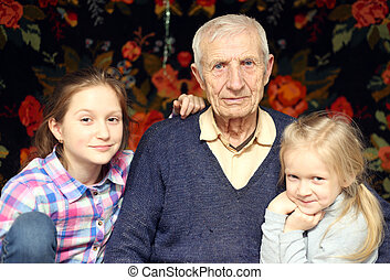 senior man with granddaughters - portrait of sitting senior...