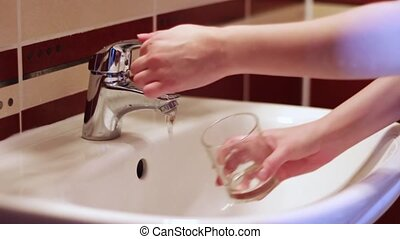 Man collects the water in a glass of tap water - Human hand...