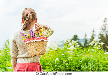 Portrait of a cute little girl with basket with flowers