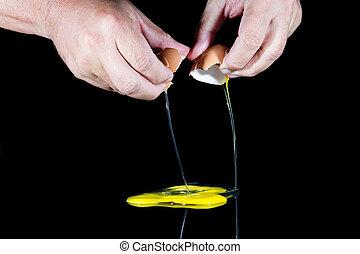 Two hands break egg on black background