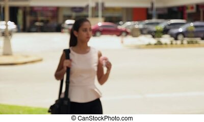 Business Woman Eating Donut - Young business woman walking...