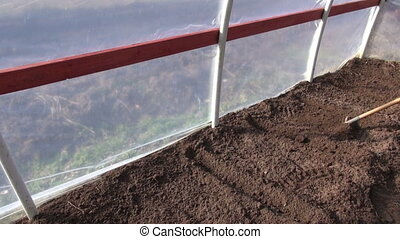 rake soil in greenhouse - rake soil earth in spring time...