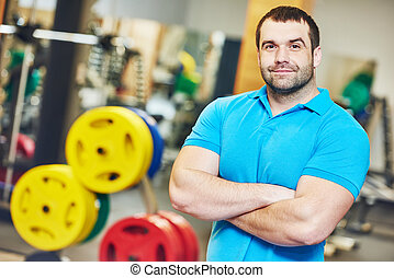male fitness trainer at gym - Portrait of a smiling male...