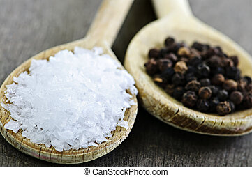 Salt and pepper - Sea salt and whole peppercorns on wooden...