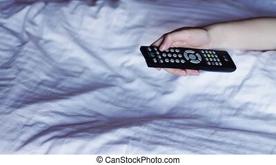 Switching channels on your TV remote control - Man lying on...
