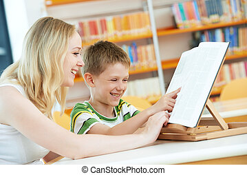 young woman and boy reading book in library