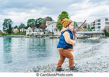 Cute toddler boy playing next to lake