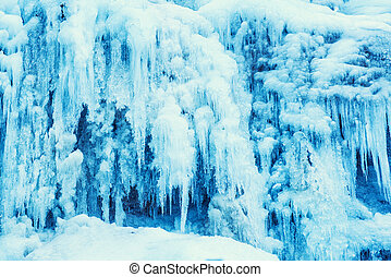 Frozen waterfall of blue icicles on the rock