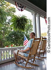 Sitting Adult Man at the Terrace with USA Flags