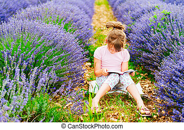 Adorable little girl reading a book in a lavender field on a...