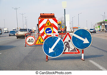 Road works: signs on the lane to warn the drivers of the...