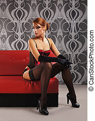 Young and beautiful redhead cabaret dancer in the chair over...