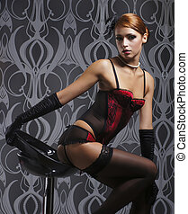 Young and beautiful redhead cabare dancer in the chair over...