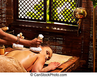 Woman having massage with pouch. - Woman having Ayurveda...
