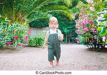 Adorable toddler boy walking with flowers in his hand