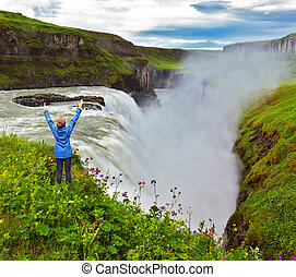 Woman thrilled looking at the abyss - Powerful Gullfoss in...