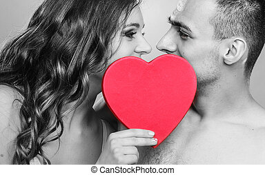 romantic couple kissing behind red heart - Attractive young...