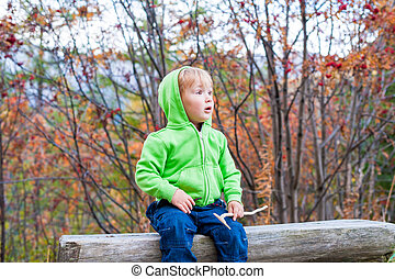 Cute toddler boy resting in a forest, wearing jeans and...