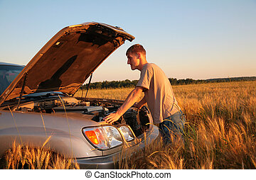 Man in wheat field with hood up on his car