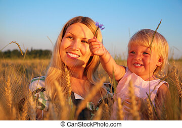 Mother with  child sit in wheat field with cornflower
