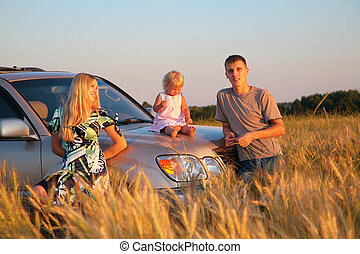 Parents and child sitting on car hood in wheat field