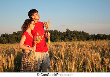 Couple in field with wheat in hands