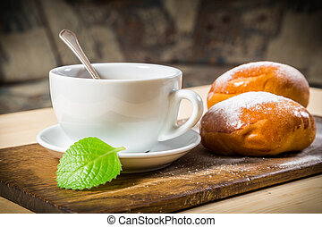 Tea cup with two buns on table - Tea cup with two buns on...