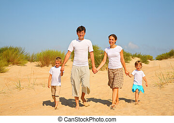 Family of four walk on sand