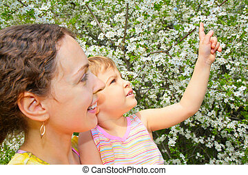 mother and daughter look on blossom cherry