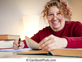 professor jew over books smiling - mature female is sitting...
