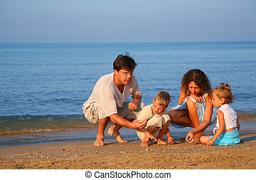 Parents play with children finding shells on sand at edge of sea
