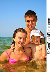 Family with little girl pose in sea