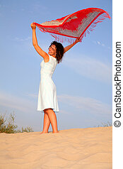 Girl on sand with shawl in hands