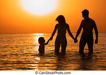 Parents with child in sea on sunset