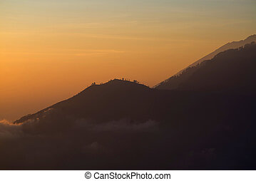 Batur - Sunrise yellow view on rocky mountine from Batur,...