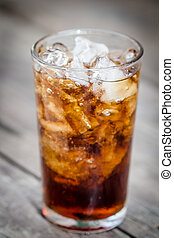 brown soda - a glass of brown soda with ice cubes on wooden