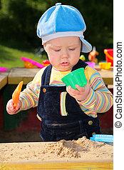 little child plays in sandbox