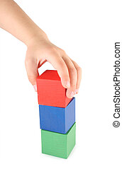 Childrens hand and toy cubes