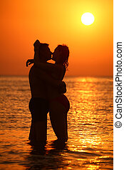 Couple silhouette ebraces and kisses in sea on sunset