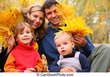 Family of four with yellow maple leaves in wood in autumn