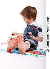 Boy painting - Funny photo of cute 5 years old boy painting...