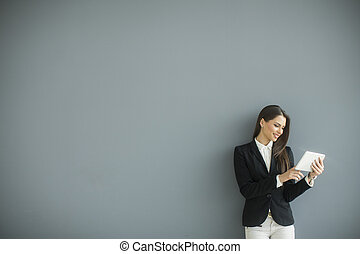 Young woman with tablet by the grey wall