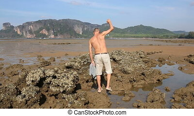 old man walks along stones at low tide