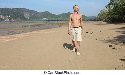 old man of athletic build  walks along sand beach