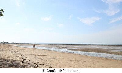 old man runs along beach at low tide