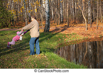 Grandfather rotates  granddaughter  in wood in autumn near pond
