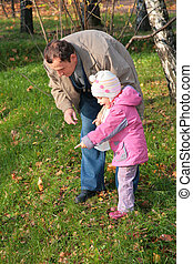 Grandfather with  granddaughter outdoor look downward