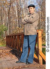 Portrait of elderly man in black hat in wood in autumn on...