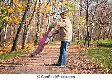 Grandfather rotates  granddaughter  in wood in autumn