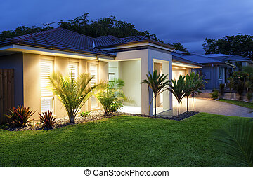 New home at dusk - Well lit modern home exterior at dusk